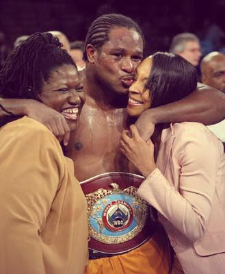Боксёр обнимает двух женщин