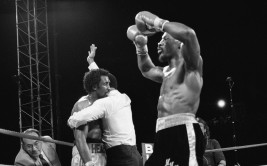 """Challenger Marvelous Marvin Hagler holds his arms up in victory as referee Richard Steele holds up defending champion Thomas """"Hit Man"""" Hearns and signals the end of the world middleweight championship bout at the outdoor stadium at Caesars Palace in Las Vegas, Nev., Monday, April 15, 1985.  Hagler won after his third round knock-out.  (AP Photo)"""